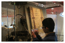 A student examines a historical artefact at the National Museum of Australia